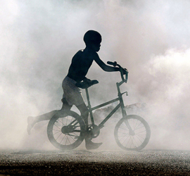 A Haitian boy runs with a bicycle in front of smoke of the garbages burned in the neighbourhood of Cite-Soleil